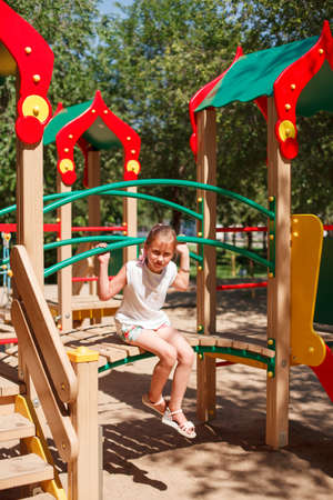 Cute blonde little girl is playing at playground. She is sitting on the little bridge Stock Photo