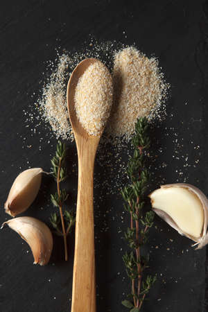 Vertical photo of garlic powder sprinkled into wooden spoon, two sprigs of thyme and thre cloves on black slate board. Selective focus Stock fotó
