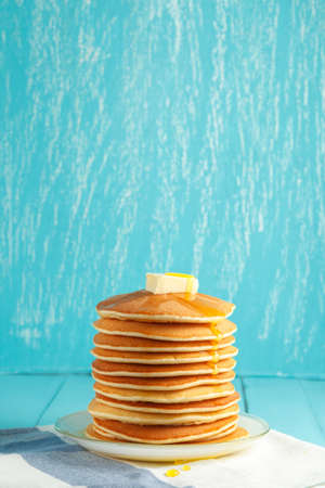 Stack of pancakes with honey and piece of butter on plate which stands on napkin on blue wooden table. Copyspace. Concept of shrovetide treats or tasty food. Selective focus Stock Photo