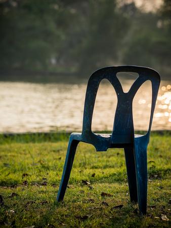 broken back: Three-legged plastic chair in garden Stock Photo
