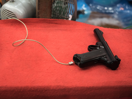 black toy gun on red table at a Temple Fair in Bangkok , Thailand
