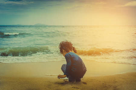 looking at baby: A lonely girl sitting on the beach Stock Photo