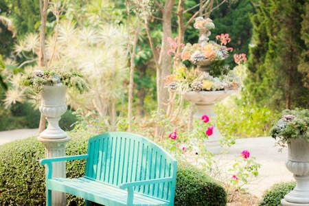 flower garden path: Blue garden bench in decorative outdoor garden with relaxing atmosphere