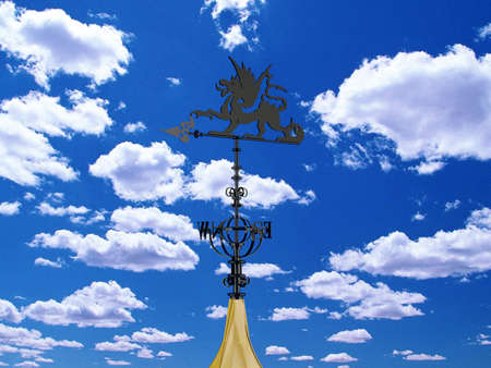 windward: Dragon weather vane isolated with clouds blue sky as background