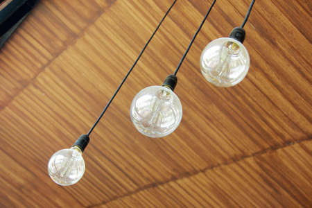 home interior: Three retro light bulbs hanging from wood ceiling in coffee shop