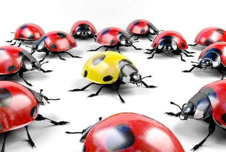 Yellow ladybug surrounded by group of red ladybugs, stock image representing unacceptable, different, underdog, mutant concept Stock Photo