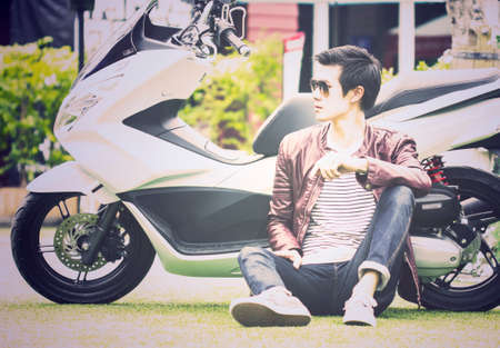 sitting on the ground: Asian man sitting on ground with his scooter outdoor, stock image