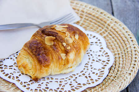 epicure: Almond croissant isolated on wooden dish