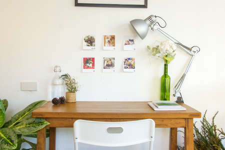desk area: Wooden table and decorative elements in white room Stock Photo