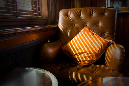 leather sofa: Brown leather sofa chair nearby window Stock Photo