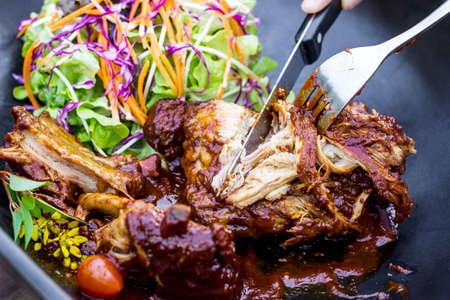Steak knife and fork slicing grilled rib eye beef steak with vegetable salad in black bowl