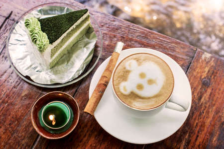 cinnamon stick: Cappuccino coffee with cinnamon stick and green tea cake on table with candle Stock Photo