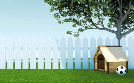 Wooden dog kennel under tree shade on green grass meadow with soccer ball and white wooden fence