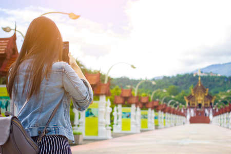 Female tourist taking picture of Buddhist temple in Chiangmai, Thailand with mobile smart phone
