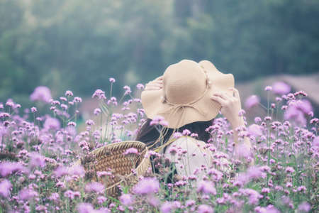Woman wearing sun hat and bamboo basket visiting Verbena flower field. Image with film camera filter.