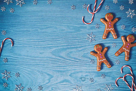Christmas background. Gingerbread man, Christmas candy cane and snowflakes on blue wooden background with copy space for text, 3D rendering