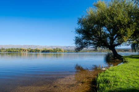 The artificial lake or 'La Florida' in the Argentinian province or San Luis attracts local tourists. You can enjoy a swim or the view, like this one with a tree hanging over the blue reservoir.