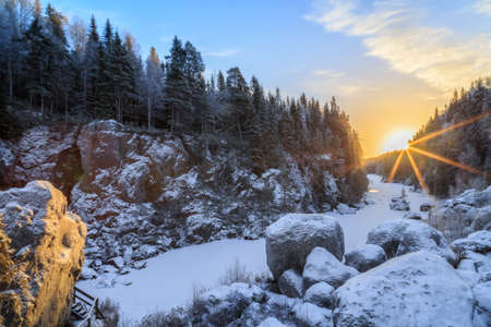 rocks with sun flares in a river, forest , winter landscape