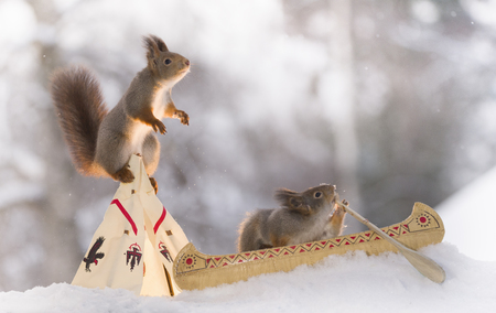 two Red squirrels with a teepee and a canoe Stock Photo