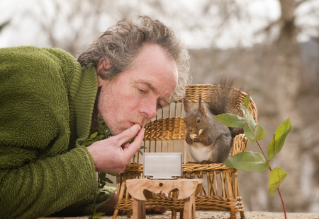 man with an red squirrel watching television