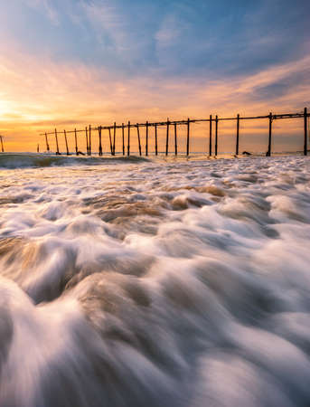 Sunset,wave,old pier at old pier Pilai beach in Phang Nga ,Thailand