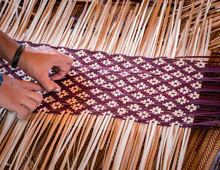 Close up Hands  weaving a woven mat   Thais artwork.