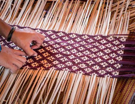 Close up Hands weaving eine gewebte Matte Thai's Artwork.