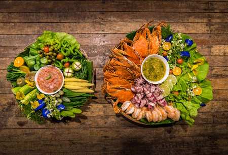 Thai chili sauce or Nam Prik and vegetable set (eggplant,aubergine,lentils,cucumber,corn,zucchini) and Seafood set (shrimp,crab,squid) with Thai sauce On a wooden table , local food Southern Thailand Stock Photo