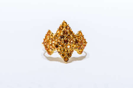 finery: Gold ring with pebble on white background