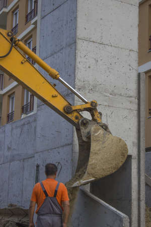 Construction Worker and excavator arm in action, at the construction site. photo