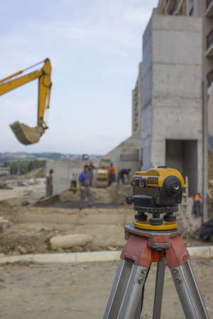 surveyors: Surveyors on a construction site, excavator is beyond depth of field. Stock Photo