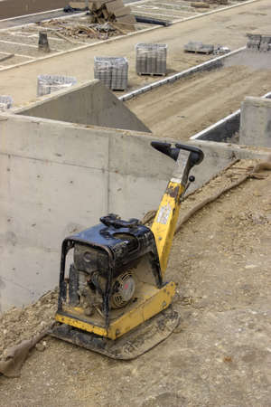 blacktopping: Vibrating machine for compacting soil at the construction site.