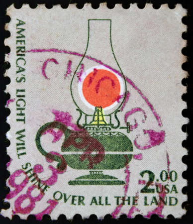 USA postage stamp Americas Light Will Shine Over All the Land 2$, shows a kerosene table lamp. photo