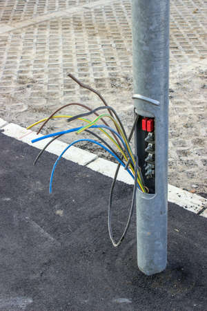 Copper wires in street light pole, small plate missing. By pulling up three or four copper wires that connect one light pole to the next, thieves can steal as much as three to four hundred yards of wire from one pole.