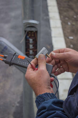 manual test equipment: Electrician testing a circuit breaker from street light pole