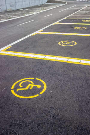 Handicap parking space just painted. Universal wheelchair symbols painted on the asphalt. Focus is on the at the first sign of wheelchair symbols. Stock Photo - 23803835