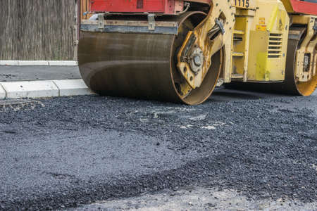 asphalting: compactor roller during road construction at asphalting work Stock Photo