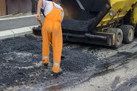 Asphalt paver machine during road construction, man is working, apply the first layer of asphalt.