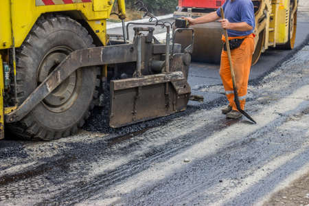 vibroroller: Asphalt paver machine and compactor roller during road construction, man is working, apply the first layer of asphalt.