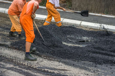 construction crew: Road construction crew apply the first layer of asphalt Stock Photo