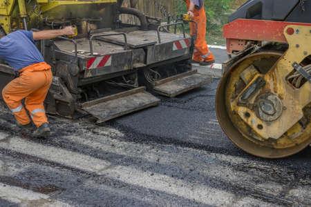 construction crew: Asphalt paver machine during road construction, road construction crew apply the first layer of asphalt.