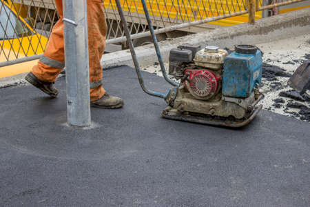 jack tar: Asphalt worker with compactor plate in use on tarmac, compacts asphalt around the lamppost where inaccessible to large machines.