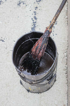 emulsion: Bitumen Emulsion (Tack Coats) in metal bucket. Tack coat is a browny-black emulsion of bitumen that is applied to the prepared, existing surface before laying the new surfacewearing course.  Stock Photo