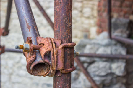 holdfast: Detail of vintage and rusty scaffolding clamp with pipes Stock Photo