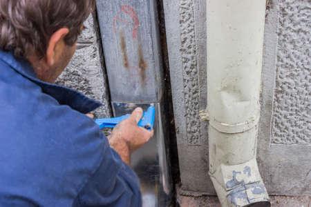 Festsetzung einer undichten Dachrinne Fallrohr, Befestigungs eine undichte Dachrinne, Dachrinnen undicht Patchen Standard-Bild - 23985513