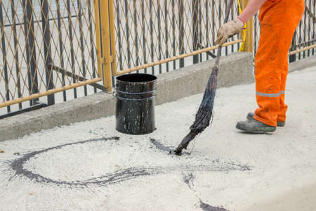 to ensure: Asphalt worker apply tack coat with a broom to a concrete before paving. Asphalt tack coat is used to ensure a good bond.  Stock Photo