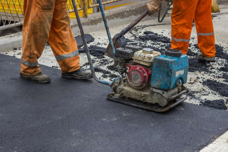 jack tar: Asphalt worker with compactor plate in use on tarmac