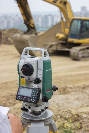 Land surveyor working with total station at construction site photo