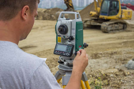 land surveyor: Land surveyor working with total station at construction site