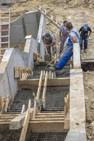 manual workers pouring concrete steps on the building site photo